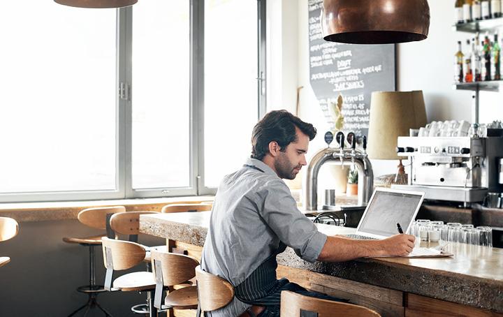 Man working on laptop at bar